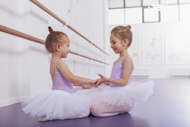 バレエ学校でお互いに微笑んで手を繋いでいる2つの愛らしい小さなバレリーナ。練習後休んでかわいい幸せな若いバレエダンサー