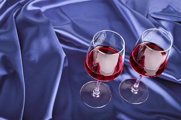 青い絹の赤ワインと2つのワイングラス