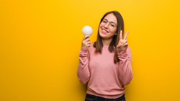 番号2を示す電球を保持している若いかわいい女性