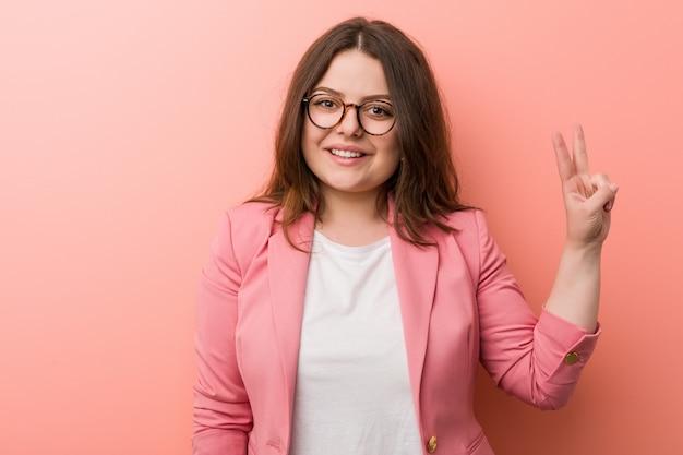 若いプラスサイズの白人女性が指で2番目を示しています。