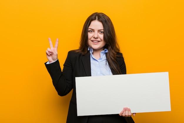 指で2番目を示す空白のプラカードを保持している若いプラスのサイズの曲線の女性。