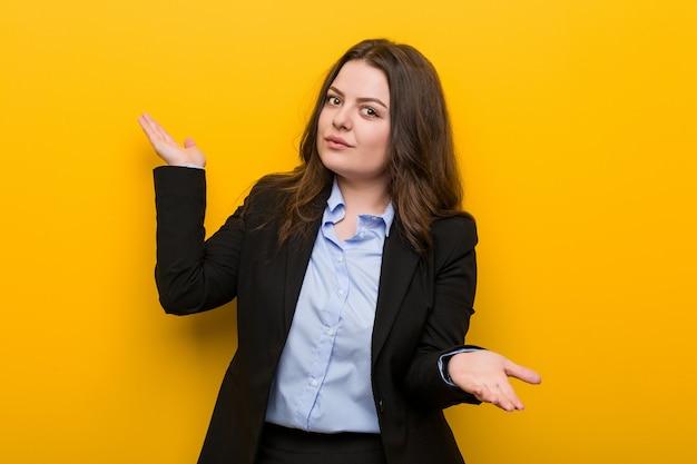2つのオプションの間を疑っている若いプラスのサイズの白人ビジネス女性。