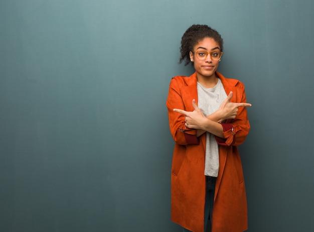 青い目を持つ若い黒人アフリカ系アメリカ人の女の子は2つのオプションの間を決定します。