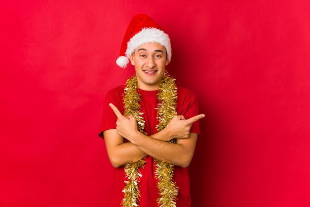 クリスマスの日の若い男は横向きのポイント、2つのオプションの間で選択しようとしています。