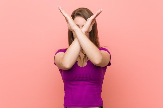 2本の腕を維持するピンクの壁に対して若いヒスパニック系女性が交差、拒否の概念。