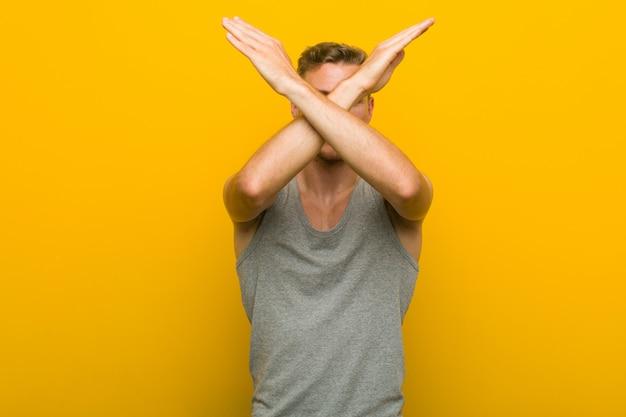 2つの腕を維持する若い白人スポーツ男が交差、拒否の概念。