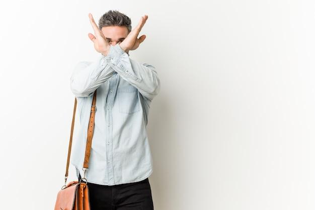 2本の腕を維持する若いハンサムなビジネスマンが交差、拒否の概念。