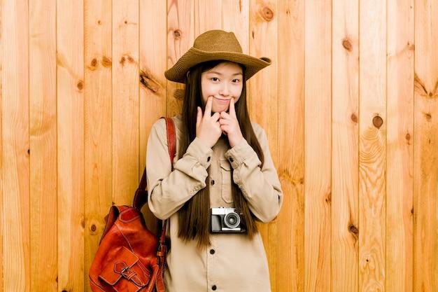 Молодая китайская женщина путешественника сомневаясь между 2 вариантами.