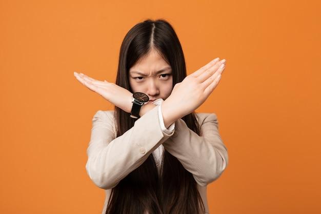 若いビジネス中国人女性が2本の腕を組んで、拒否の概念を維持します。