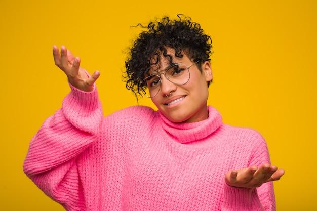 Молодая афро-американская женщина нося розовый свитер сомневаясь между 2 вариантами.