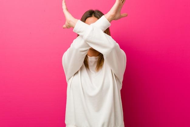 2本の腕を組んで、否定的な概念を維持する壁に若い本物のカリスマ的な実在の女性。