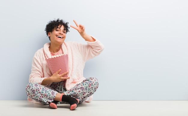 指で番号2を示すポップコーンバケツを保持している若いアフリカ系アメリカ人女性。