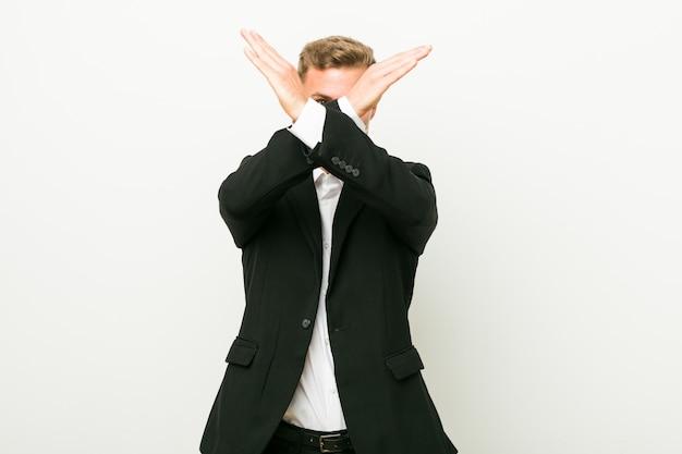 2つの腕を維持する若い白人ビジネスマンが交差、拒否の概念。