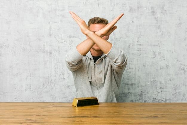 2本の腕を組んで、否定的な概念を維持するテーブルに金塊を保持している若いハンサムな男。
