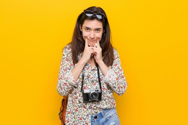 2つのオプションの間を疑う若いブルネット旅行者女性。