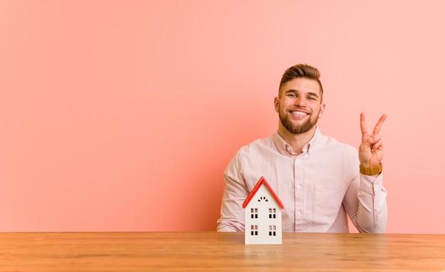 指で2番目を示す家のアイコンと座っている若い白人男。
