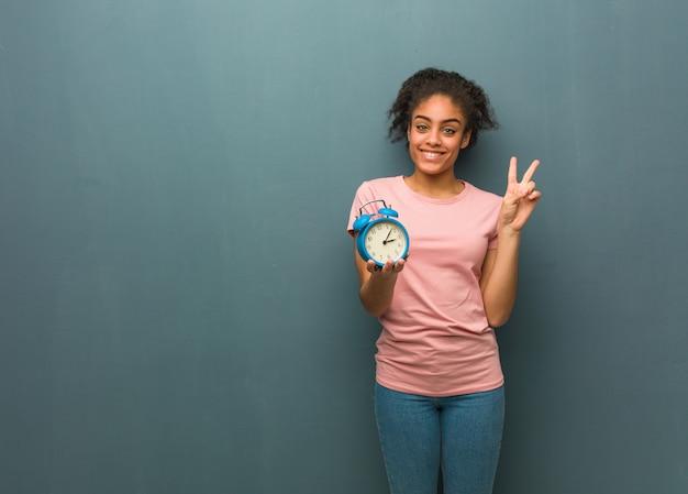 番号2を示す若い黒人女性。彼女は目覚まし時計を持っています。