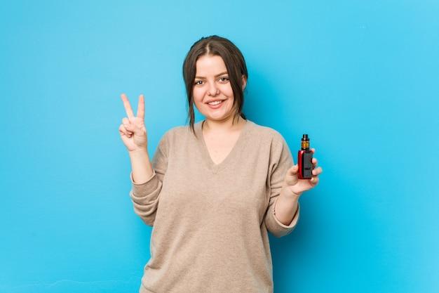 指で番号2を示す気化器を保持している若い曲線の女性。