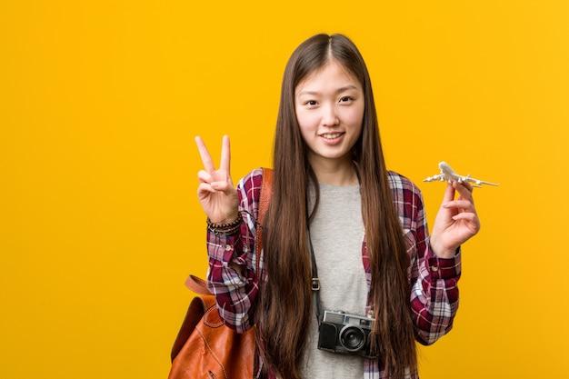 指で2番目を示す飛行機アイコンを保持している若いアジア女性。