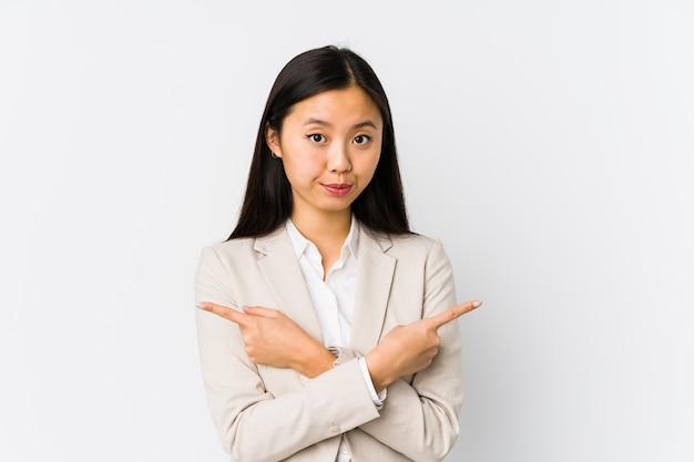 若い中国のビジネス女性は横向きにポイントを分離し、2つのオプションから選択しようとしています。