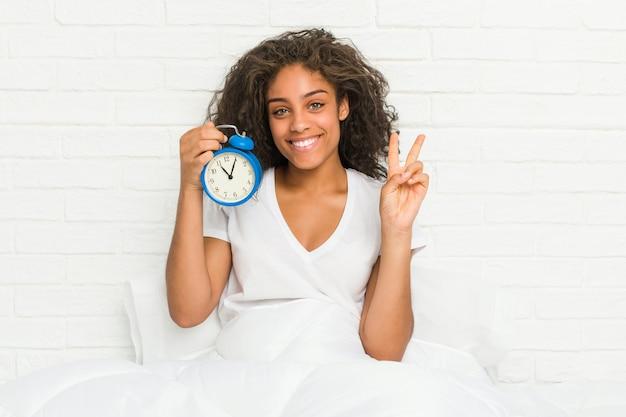 指で番号2を示す目覚まし時計を保持しているベッドに座っている若いアフリカ系アメリカ人女性。