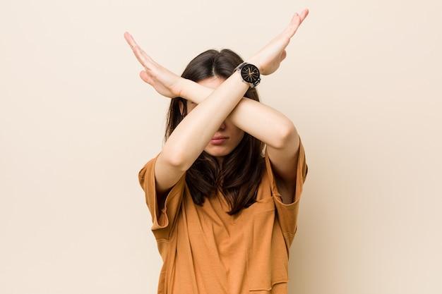 Молодая женщина брюнет против бежевой стены держа 2 оружия пересекла, концепция отказа.
