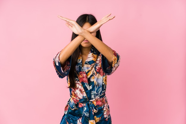 Молодая азиатская женщина нося пижамы кимоно держа 2 оружия пересекла, концепция отказа.