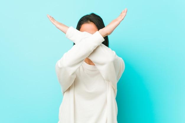若いかなりヒスパニック系女性が2本の腕を組んで、拒否の概念を維持します。