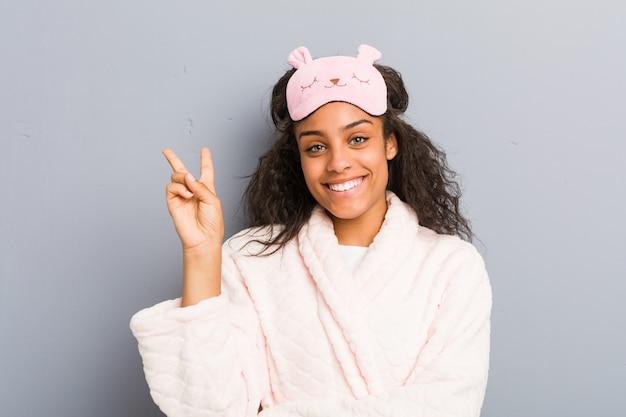 パジャマと睡眠マスクを身に着けている若いアフリカ系アメリカ人女性は、指で2番を示します。