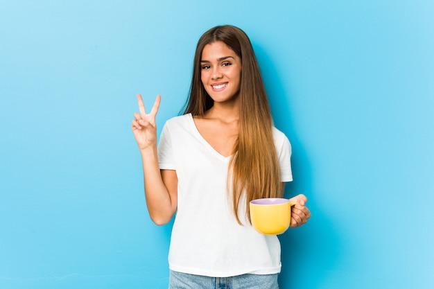 指で番号2を示すコーヒーのマグカップを保持している若い白人女性。