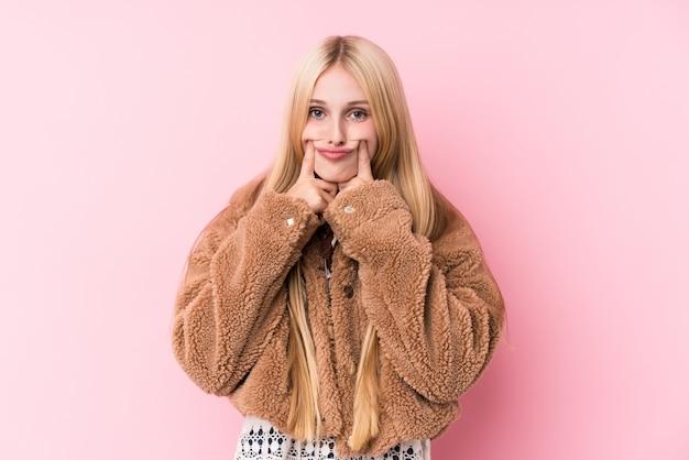 2つのオプションの間を疑うコートを着ている若いブロンドの女性