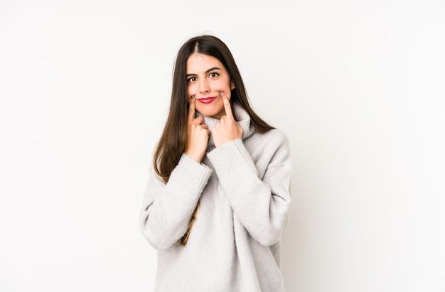 Молодая кавказская женщина на белой стене сомневаясь между 2 вариантами.