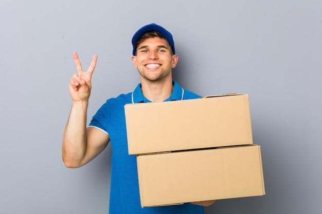 指で2番目を示すパッケージを提供する若い男。