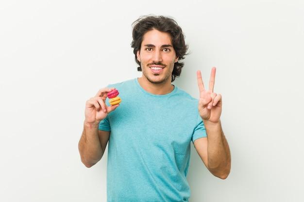 若い男が指で数2を示すマカロンを保持しています。