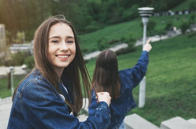 都市公園を歩いて2つのスタイリッシュな幸せな女の子