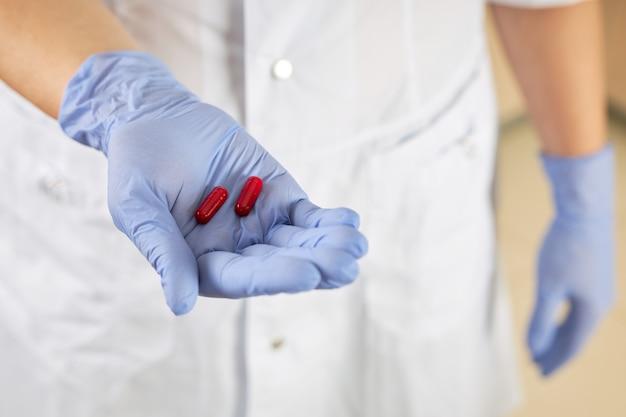ウイルスの治療法として、看護師は手のひらに2つの赤い錠剤を保持しています