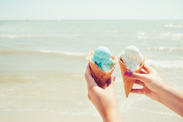 女性の手は海に2つのアイスクリームを保持しています。