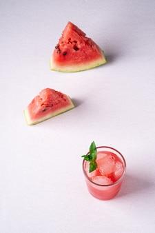 新鮮な冷たいスイカジュース、アイスキューブと2つのスライスのスイカに近いガラスの飲み物に緑のミントの葉