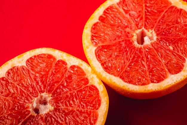 グレープフルーツ2つの半分の果物、熱帯の創造的な最小限の食品のコンセプト、鮮やかな赤い背景、緑豊かな溶岩、アングルビューの選択と集中