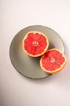 グレープフルーツ2半分グレープレート、トロピカルクリエイティブな最小限の食品フルーツコンセプト、白い背景、鮮やかな色、トップビューの選択と集中
