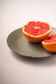 グレープフルーツ2半分グレープレート、トロピカルクリエイティブな最小限の食品フルーツコンセプト、白い背景、鮮やかな色、アングルビューの選択と集中