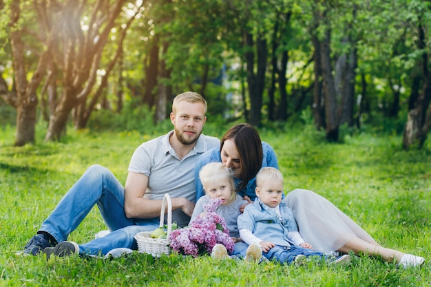 2人の子供を持つ家族は、夏の庭で休みます