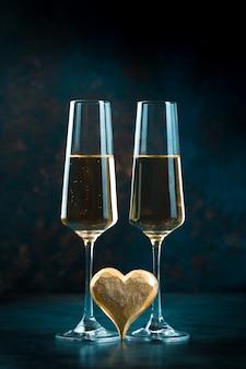 黄金の心と輝く黄金のシャンパンと2つのエレガントなロマンチックなメガネ。バレンタインデーのコンセプト