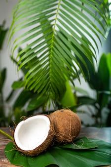 2 кокоса одного раскрытого лежать на деревянном столе среди зеленой листвы