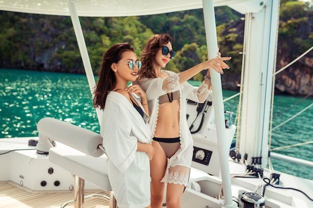 海でヨットで旅行する2つのガールフレンド