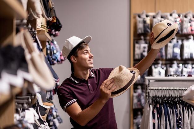 かわいい笑顔の若い男が物事を棚に立ち、頭に帽子をかぶって2つの麦わら帽子をかぶった店で浮気ポーズをとります。楽しい感情。販売。ショッピング。