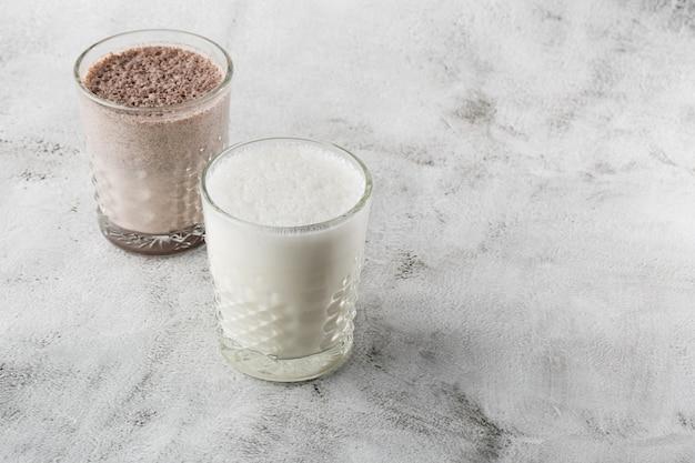明るい大理石の背景に分離されたアイスココアまたはチョコレートミルクを2杯。俯瞰、コピースペース。カフェメニューの宣伝。コーヒーショップメニュー。横の写真。