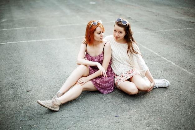 遊び場に座っている2人の十代女の子
