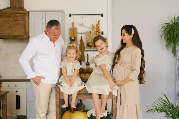 新しい家族を待っているキッチンで幸せと笑顔の2人の娘と美しいフレンドリーな家族。妊娠中のママ