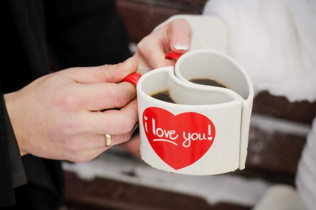 新郎新婦の手の中にハートの形の2つの白いマグカップ。バレンタインデー、愛と結婚の日